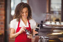 A smiling barista pressing coffee Royalty Free Stock Photos