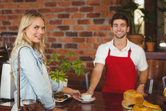 Smiling barista serving a client Royalty Free Stock Photography