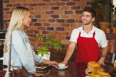 Smiling barista serving a client Royalty Free Stock Image