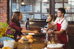 A smiling barista serving a client Stock Image