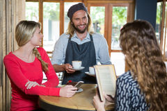 Smiling barista serving coffee to female customers in cafe. Smiling male barista serving coffee to female customers in cafe Royalty Free Stock Photos