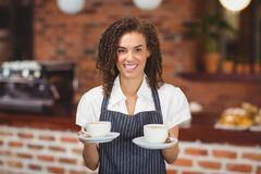 Smiling barista serving two cups of coffee Royalty Free Stock Photos