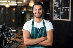 Smiling barista standing with arms crossed Stock Photo