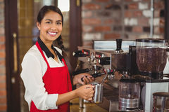 Smiling barista steaming milk at the coffee machine. Portrait of a barista steaming milk at the coffee shop royalty free stock image