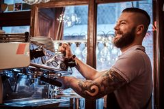 Smiling barista with stylish beard and hairstyle making coffee for a customer in the coffee shop. Cheerful barista with stylish beard and hairstyle making coffee royalty free stock photos