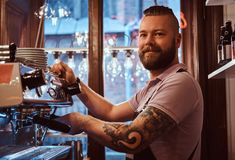 Smiling barista with stylish beard and hairstyle making coffee for a customer in the coffee shop. Cheerful barista with stylish beard and hairstyle making coffee stock image
