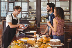 Smiling barista taking credit card from hipsters. At coffee shop stock image
