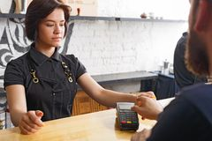 Smiling barista taking payment from client at counter of a coffee shop. Beautiful smiling barista giving POS terminal to customer with credit card at coffee shop Stock Photos