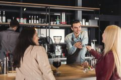 Smiling barista taking payment from clients. Smiling barista taking credit card from customers to pay for beverage at coffee shop counter. Small business Royalty Free Stock Photos