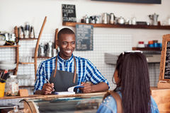 Smiling barista talking to a customer in his cafe. Smiling young African barista standing at the counter of a cafe talking to a customer and writing down an Stock Photos