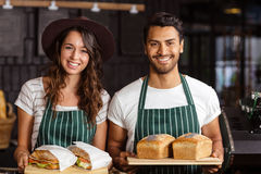 Smiling baristas holding bread and sandwiches Stock Image