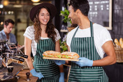 Smiling baristas holding sandwiches Royalty Free Stock Image