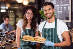 Smiling baristas holding sandwiches Royalty Free Stock Photography
