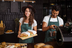 Smiling baristas holding sandwiches and making coffee Royalty Free Stock Image