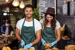 Smiling baristas preparing sandwiches Royalty Free Stock Photography