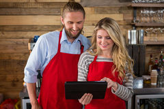 Smiling baristas using digital tablet in coffee shop Royalty Free Stock Images