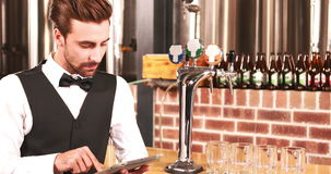 Smiling barkeeper using tablet well dressed. At bar stock footage