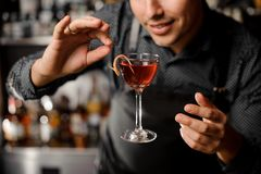 Smiling barman with a glass filled with alcoholic drink in the air Royalty Free Stock Images