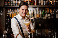 Smiling barman holding coctail at the bar stand Royalty Free Stock Image