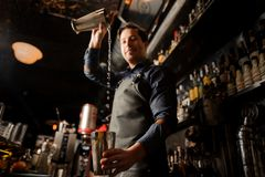 Smiling barman pouring alcoholic drink from one metal glass into another Stock Photography