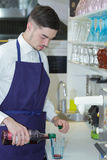 Smiling barman at work he prepares cordials Royalty Free Stock Images