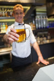 Smiling bartender offering pint of beer to camera Royalty Free Stock Images