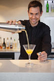Smiling bartender pouring cocktail into glass Stock Images