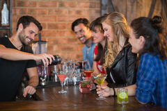 Smiling bartender serving drink for customers. In pub Royalty Free Stock Photos