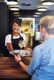 Smiling bartender serving glasses of white wine Stock Photo