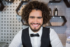Smiling bartender standing in bar counter. Portrait of smiling bartender standing in bar counter Stock Photography