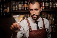 Smiling bartender holding a transparent cocktail in the martini. Smiling bartender in the white shirt and brown leather apron holding a transparent cocktail in royalty free stock image