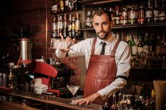 Smiling bartender pourring a transparent cocktail into the cocktail glass stock photo