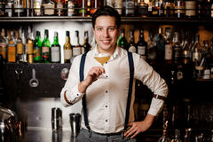 Smiling bartender in white shirt with cocktail. At the bar stand Royalty Free Stock Image