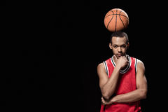 Smiling basketball player standing with ball on head on black Royalty Free Stock Image