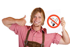 Smiling Bavarian man holds no-smoking-rule sign Royalty Free Stock Image