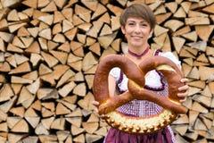Smiling Bavarian woman holding a large pretzel royalty free stock image