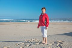 Smiling beach granny. That is what Kleinbrak beach looks like on a lovely winter aftern at 17h00. My dear wife kindly agree for a few shots and the red jacket stock images