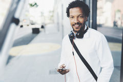 Smiling bearded African man holding smartphone in hands while standing at sunny city street.Concept of happy business Royalty Free Stock Photos