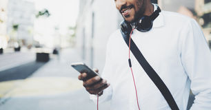 Smiling bearded African man holding smartphone on hands while standing at sunny city street.Concept of happy business Stock Images