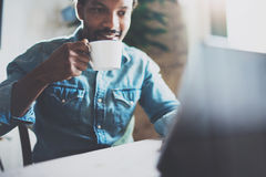 Smiling bearded African man making video conversation via laptop with partners while drinking white cup black tea in Royalty Free Stock Photos