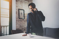 Smiling bearded African man talking on smartphone while standing near wooden table in his modern home.Concept of young. Business people working at home.Blurred Stock Image