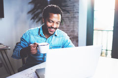 Smiling bearded African man using laptop home while drinking cup black coffee at the wooden table.Concept of young. People working on mobile devices.Blurred Stock Image