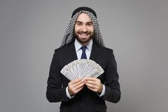 Smiling bearded arabian muslim businessman in keffiyeh kafiya ring igal agal suit isolated on gray background