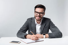 Smiling bearded bespectacled man making notes. Working atmosphere. Young handsome man smiling and making notes while sitting against white background Royalty Free Stock Photos