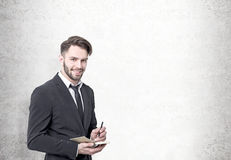 Smiling bearded businessman, concrete wall royalty free stock image