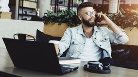 Bearded businessman,blogger sitting in cafe,talking on smart phone,working on laptop, freelancer working in coffee shop. Smiling bearded businessman in glasses royalty free stock photography