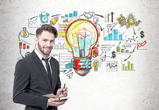 Smiling bearded businessman, light bulb, icons Stock Images