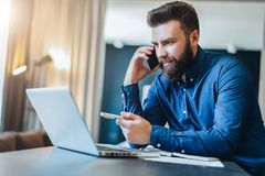 Smiling bearded businessman sitting at table in front of computer, talking on cell phone, showing pen on laptop screen. Young smiling bearded businessman is Royalty Free Stock Photos
