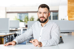 Smiling bearded businessman sitting and writing in office. Portrait of handsome smiling bearded businessman sitting and writing in office Stock Image