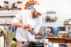 Smiling bearded chef cook standing and cooking in frying pan Stock Photos